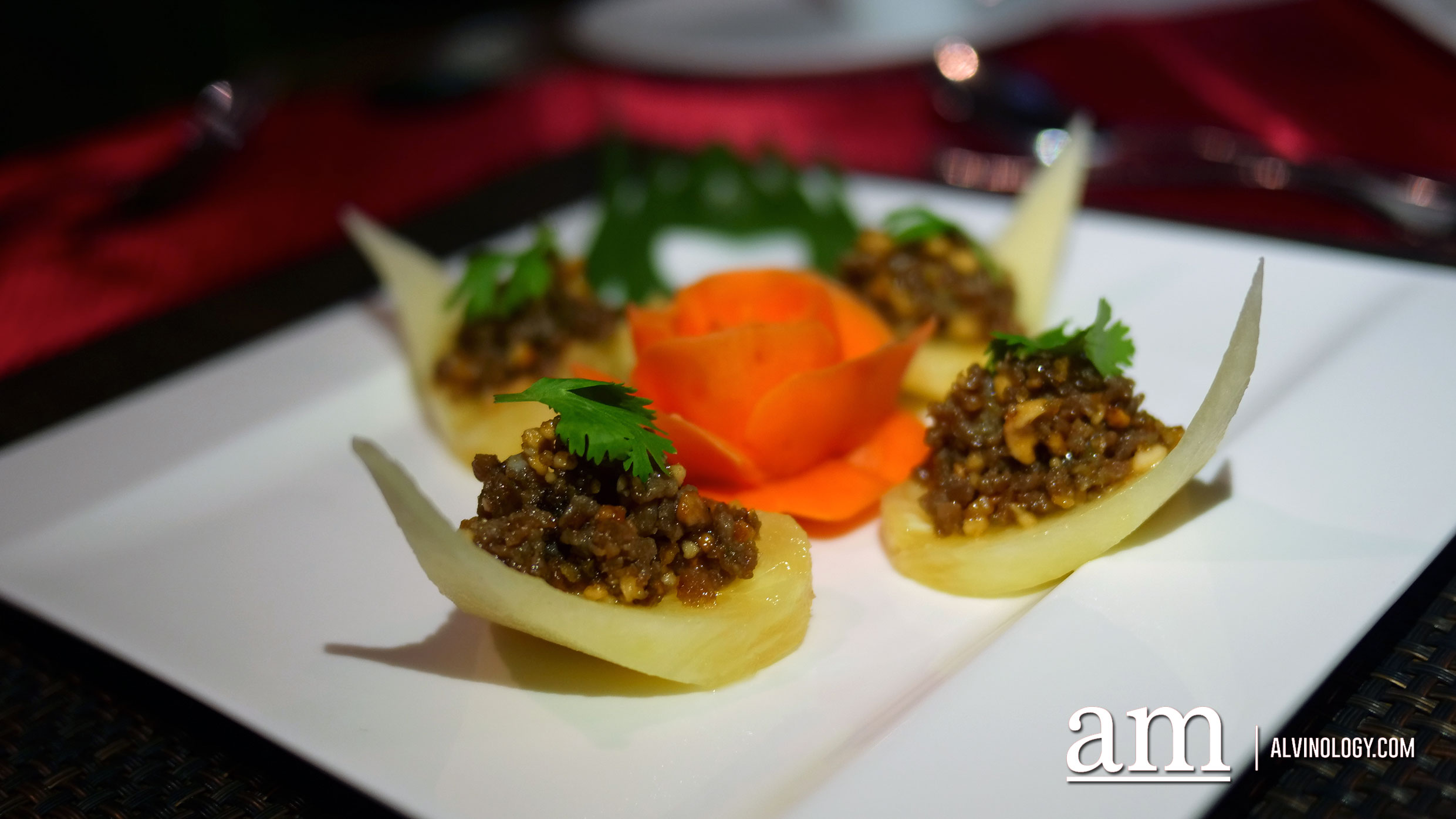 Amuse Bouche - Minced pork and prawns stir fried in a cilantro paste, seasoned with palm sugar and peanuts, served on a pineapple bite